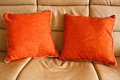 Cushions on a settee two bright orange beige leather couch Stock Photography
