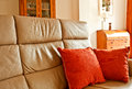 Cushions on a settee two bright orange beige leather couch in living room Royalty Free Stock Images