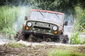 Custom built Off-road Trophy UAZ 469 leaves the swamp at high speed. Royalty Free Stock Photo
