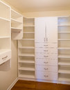 Custom closet white wood cabinetry in a walk in Royalty Free Stock Image