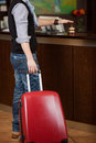 Customer with baggage ringing bell at reception counter low section of male of hotel Royalty Free Stock Photography