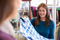Customer buying clothing in charity shop volunteer with clothes Royalty Free Stock Photography