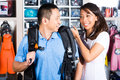 Customer buying equipment in divers shop asian a store or for an employee helping putting on the harness Stock Image
