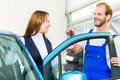 Customer and car mechanic in auto workshop female client or mot with for service inspection Royalty Free Stock Photos