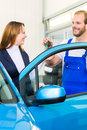 Customer and car mechanic in auto workshop