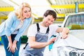 Customer and car painter in auto workshop male mechanic examine finish on dents or scratches Royalty Free Stock Images
