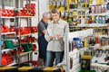 Customer choosing soldering iron in store male with worker working background at hardware Royalty Free Stock Images