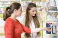 Customer in a drugstore young female pharmacist having talking about baby s feeding bottle Stock Image