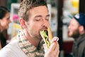 Customer eating hotdog in fast food snack bar young a delicious sausages Stock Photography