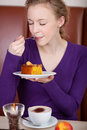 Customer with eyes closed enjoying pastry at coffee shop young female table Royalty Free Stock Image