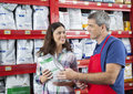 Customer looking at salesman while receiving pet food from him happy female shop Stock Photos