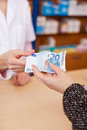 Customer s hand paying money to pharmacist closeup of at counter Royalty Free Stock Image