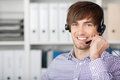 Customer service executive using headset in office portrait of handsome Royalty Free Stock Photos