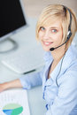 Customer service executive wearing headset at desk portrait of female while smiling office Royalty Free Stock Image