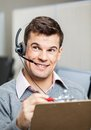 Customer service representative with clipboard happy looking away in office Royalty Free Stock Image