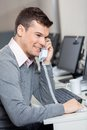 Customer service representative using landline smiling male phone at desk in office Royalty Free Stock Photos