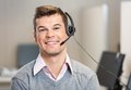 Customer service representative wearing headset portrait of confident male while smiling in office Royalty Free Stock Photo