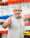 Customer showing thumbs up sign in hardware shop portrait of confident senior male Stock Image