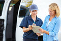 Customer signing for delivery from female courier Royalty Free Stock Photo