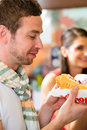Customers eating hotdog in fast food snack bar young a delicious sausages Royalty Free Stock Photo