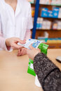Customers hand paying money to pharmacist closeup of at counter Royalty Free Stock Photo