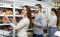 Customers near fridge with meat products Royalty Free Stock Photo