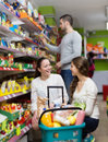 Customers standing near shelves with canned goods at shop Royalty Free Stock Photo