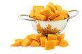 Cut butternut pumpkin blocks in a metal colander on white background Royalty Free Stock Images