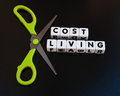 Cut cost of living text and inscribed in uppercase text on small white cubes with scissors to describe cutting dark background Royalty Free Stock Photo