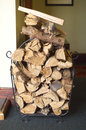 Cut firewood piled in a metal holder ready for use Royalty Free Stock Photo