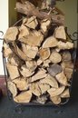Cut firewood piled in a metal holder ready for use Stock Photos