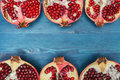 Cut in half pomegranate on a wooden blue surface: sources of vitamins and antioxidants in the winter, food for vegans Royalty Free Stock Photo