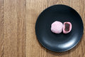 Cut mochi japanese sweet treat pink rice with filling on the black plate Stock Photos