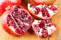 Cut open pomegranate on wooden cutting board freshly Royalty Free Stock Photos