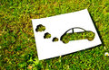 Cut paper renewable energy concept white in the shape of a car on a background of grass Stock Image