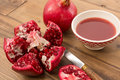 Cut pomegranate on a wooden table with bowl of juice Royalty Free Stock Photo