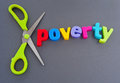 Cut poverty text in colorful lowercase letters with scissors to symbolize cutting dark background Royalty Free Stock Image