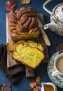 Cut the pumpkin brioche cinnamon on rustic wooden chopping board, tea with milk and a teapot on a blue background, top view. Royalty Free Stock Photo