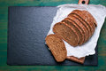 Cut in slices loaf of bread on a cut board on a green vintage wooden background with place for text Royalty Free Stock Photo