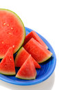 Cut watermelon on blue plate closeup of a seedless a platter half a melon surrounded by wedges of fruit vertical format a white Royalty Free Stock Image