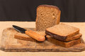 Cut wholemeal bread and knife on a chopping board Stock Photos