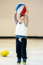 Cute adorable little small white Caucasian child toddler boy playing with ball basketball in gym on plain white light background Royalty Free Stock Photo