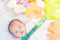 Cute adorable newborn baby playing on colorful toy