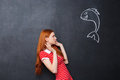 Cute afraid woman scared of shark drawn on chalkboard background