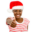 Cute african american girl fingers thumbs up sign wearing christ showing christmas hat Stock Photo