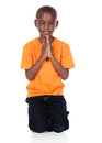 Cute african boy wearing a bright orange t shirt and dark denim jeans the is kneeling and praying Royalty Free Stock Photo