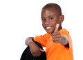 Cute african boy wearing a bright orange t shirt and dark denim jeans the is showing a thumbs up to the camera Royalty Free Stock Image