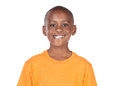 Cute african boy wearing a bright orange t shirt the is standing and smiling at the camera Stock Images