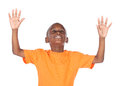 Cute african boy wearing a bright orange t shirt the is worshipping with his hands lifted up Stock Photos