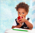 Cute african preschooler portrait of little boy sit behind a desk and biting big red apple drawing using green pencil having lunch Royalty Free Stock Image